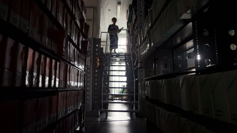 Woman librarian selects the book from a high shelf