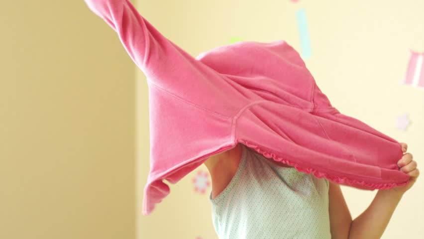 A young girl gets dressed and puts her sweatshirt on to start the day
