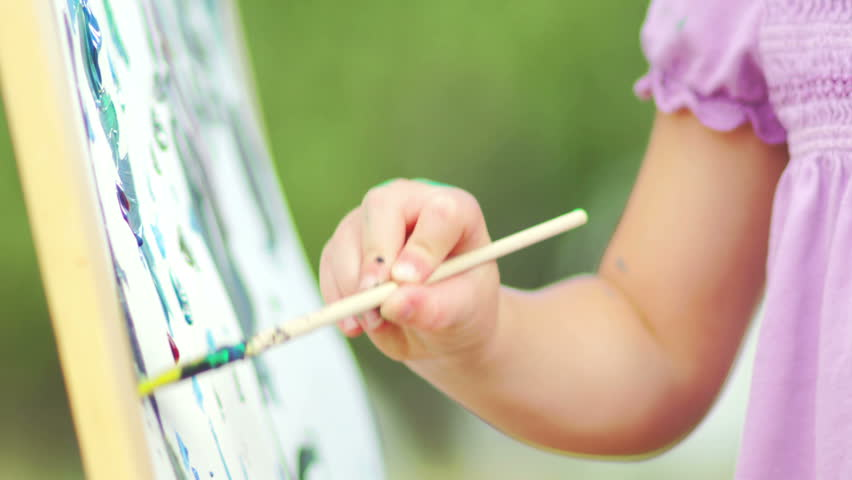 Close up of a young girl dipping her brush in paint and painting on a canvas