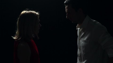 Man and woman arguing on black background. Backlit in silhouette. Studio setting in high definition video.