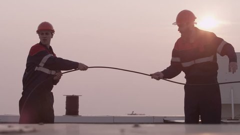 Mans Workers unwinds internet cable on the roof
