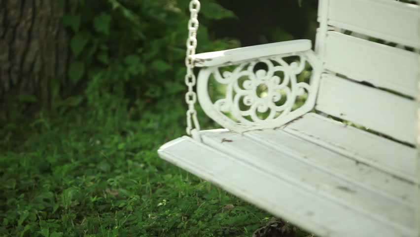 Loveseat swinging gently in a garden on a summer day. #4942637