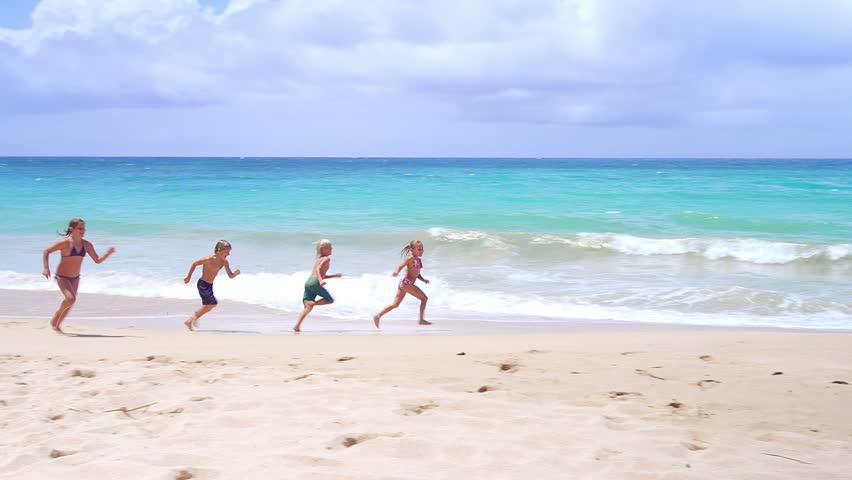 Four Kids Run Down The Beach Together Through Sand And Waves Stock Footage Video 4944116
