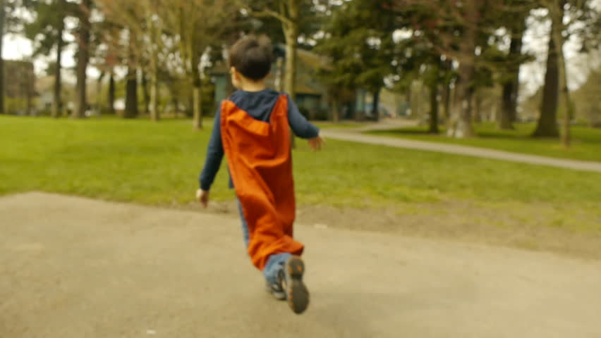 Superhero Boy Runs Around Park, Pretending to Fly
