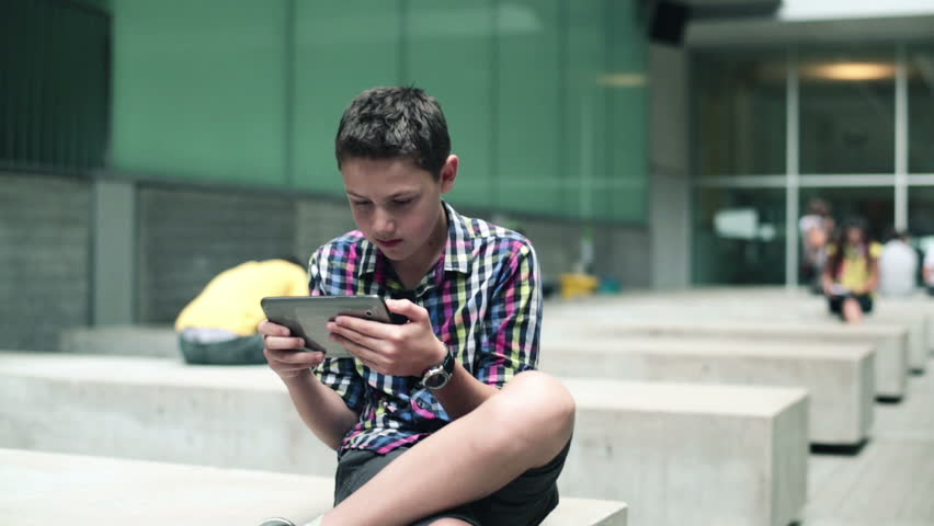 Young teenager with tablet computer in urban environment  | Shutterstock HD Video #4945586
