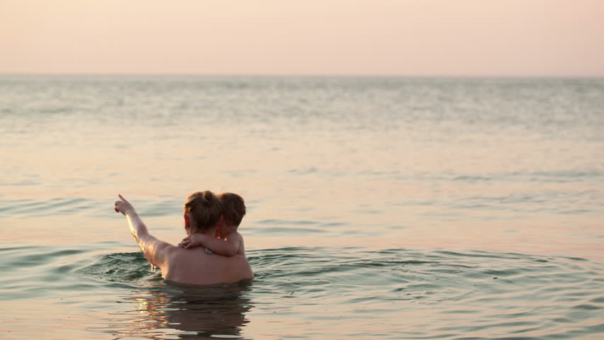 Loving mother and her young child bathing in the sea water by the beach in the sunset