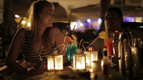 Romantic young couple enjoying drinks in a date in an outdoor bar esplanade by night