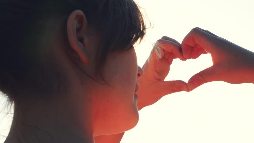 female hands making heart shape gesture holding sun flare #4982270