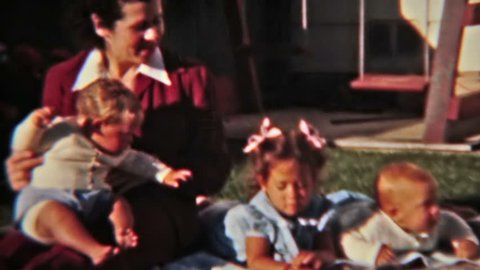 USA CIRCA 1940: Vintage homemade 8mm film of young family children and mother.  Activities and fun growing up and playing. Color retro video showing family life in the 1940's. Back yard of home.