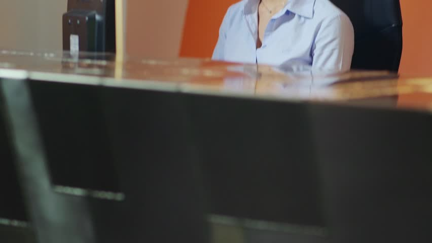 Beautiful young woman working as customer service representative at reception desk, talking on telephone with headset. 19of20
