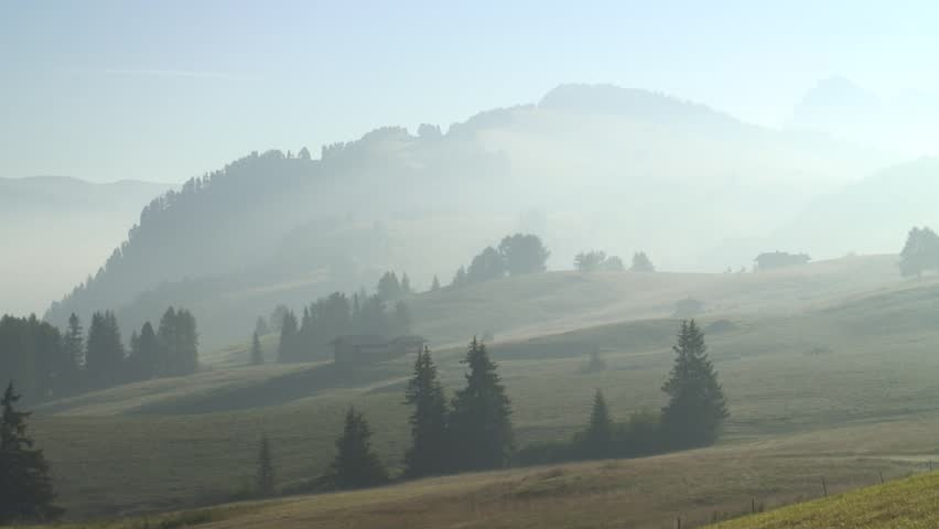 1080i: Panshot of a mountain landscape early in the morning with mist  - Alpe di Siusi - Dolomites.