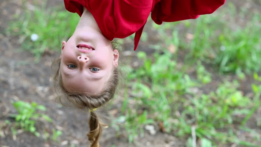 Young girl in red dress hangs upside down and then jumps to ground