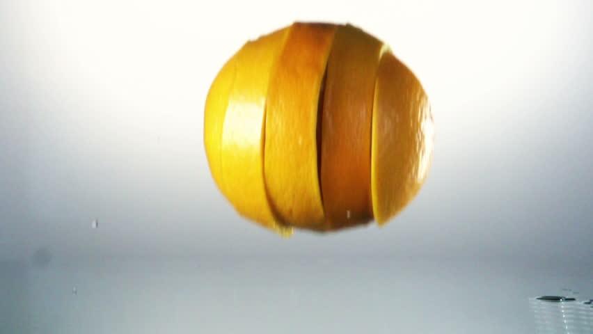 Orange slices splashing into water, slow motion