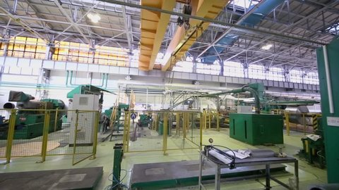 Overhead crane moves in large workshop with equipment for aluminum rolling at metallurgical factory