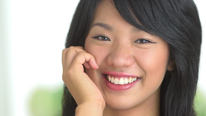 Close up of Asian woman smiling with hand on cheek