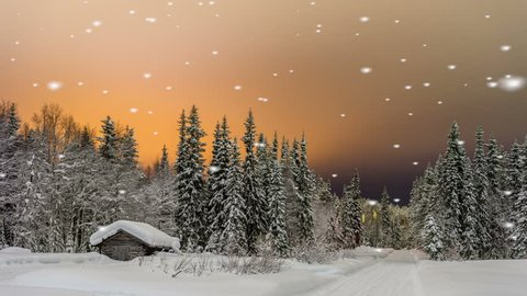 Falling snow on a quaint log cabin nestling in a snow covered evergreen forest under a beautiful glowing orange sunset sky