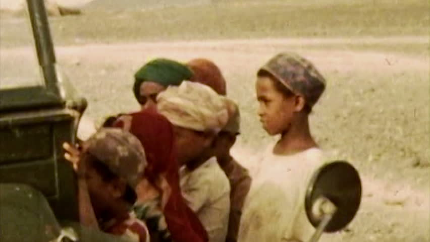 ADEN PROTECTORATE - CIRCA 1960: Bedouin children in desert in the British Aden Protectorate, southern Arabia. Vintage 8mm footage. Today territory is the Republic of Yemen.