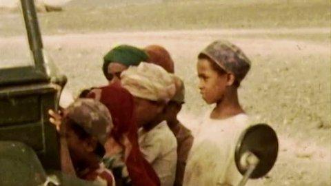 ADEN PROTECTORATE - CIRCA 1960: Bedouin children in desert in the British Aden Protectorate, southern Arabia. Vintage 8mm footage. Today territory is the Republic of Yemen.