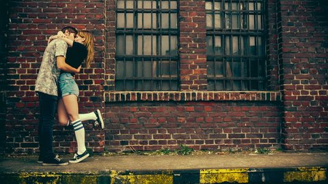 Teenage couple kissing in front of old industry building with vintage color correction