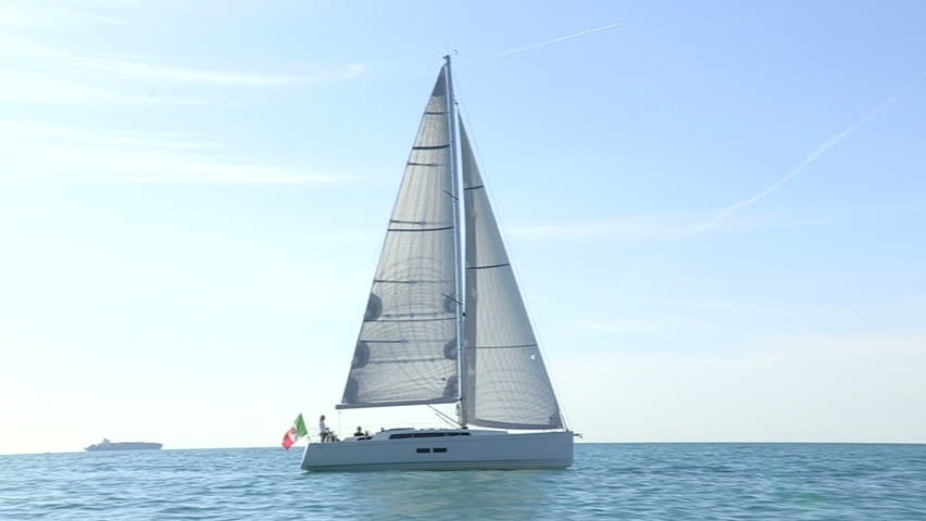Sailing boat navigating with open sails in the sea