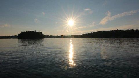 Muskoka summer lake. Sun reflected in the lake. Sun going down over Lake Rosseau, Muskoka, Ontario, Canada.