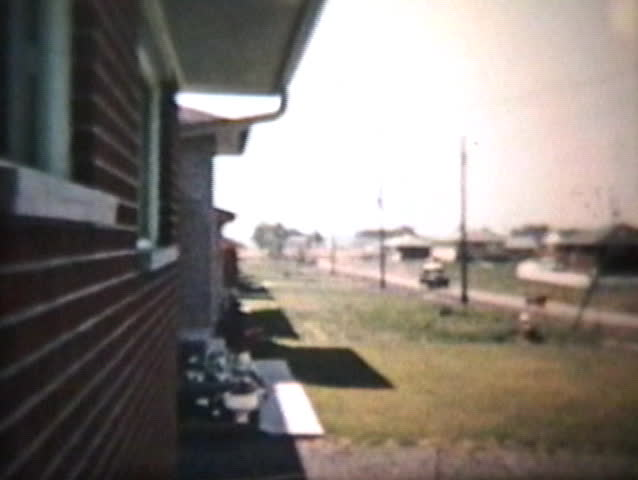 An Old Truck Passing By On A Suburban Road - Vintage 8mm film footage from 1960.