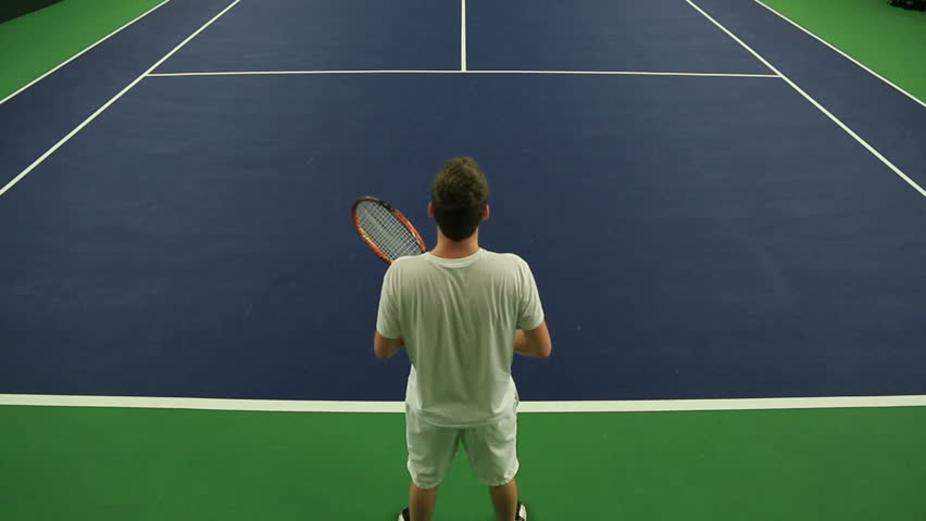 Young man practicing his Tennis skills at an indoor court