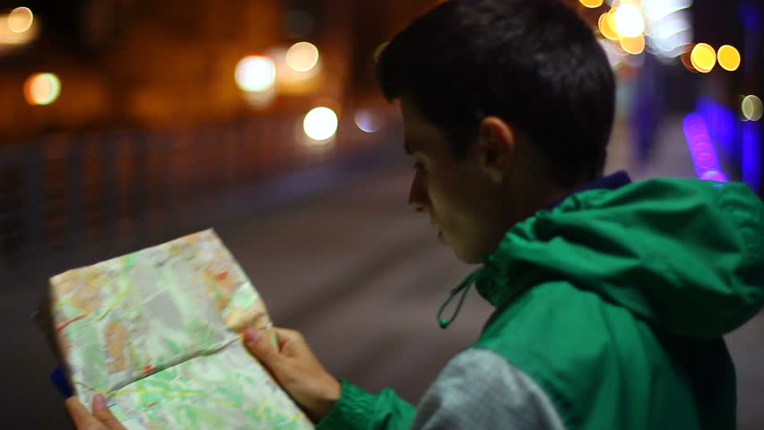 Tourist searching place location in map, lost in city night