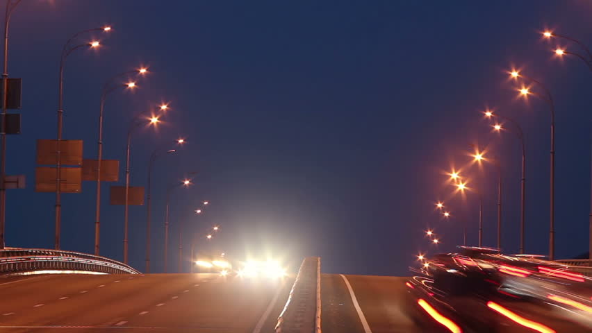 Timelapse of bridge highway traffic, dusk cars drive lights on