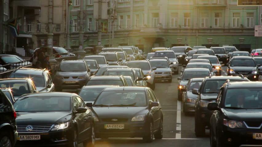 City cars vehicles lined traffic jam, dusk sun rays, movement
