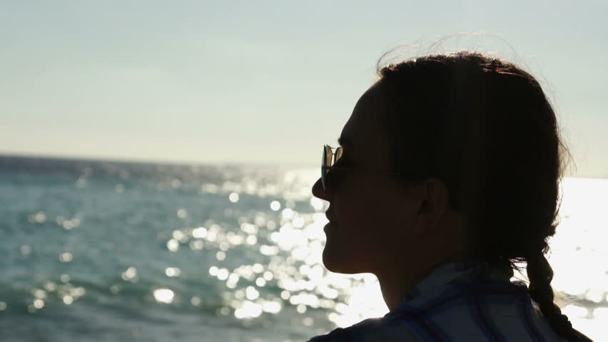 Silhouette profile of a woman looking at the sea