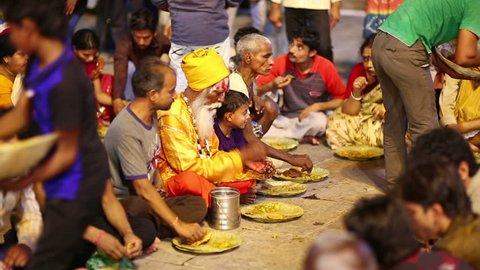 VARANASI, INDIA - MAY 2013: poor indian people eating free food at street at night