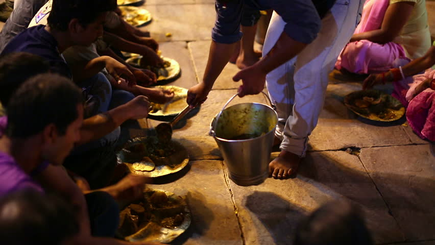 VARANASI, INDIA - MAY 2013: poor indian people eating free food at street at night