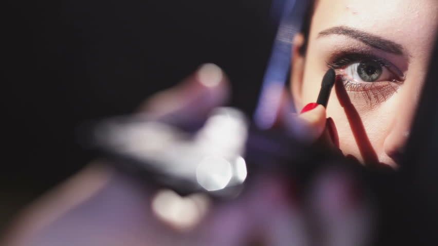 Girl in the mirror. Beautiful woman doing makeup. Reflection in the mirror