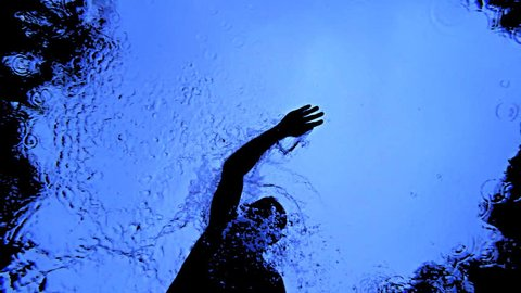 Silhouette of  a swimmer training in  a pool in the rain taken from below