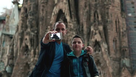Father and son taking picture of themselves by Sagrada Familia on cellphone