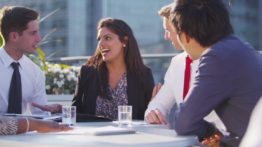 Happy mixed ethnicity business team or successful  group of friends, chatting and laughing as they sit together on an open air city roof terrace. In slow motion.   Shutterstock HD Video #5109386