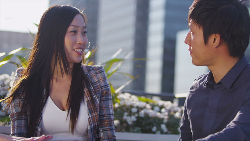 Cheerful young asian business team in a meeting on a busy open air city roof terrace. They shake hands on the completion of a deal.