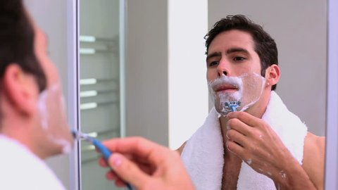 Handsome man looking at mirror and shaving in bathroom