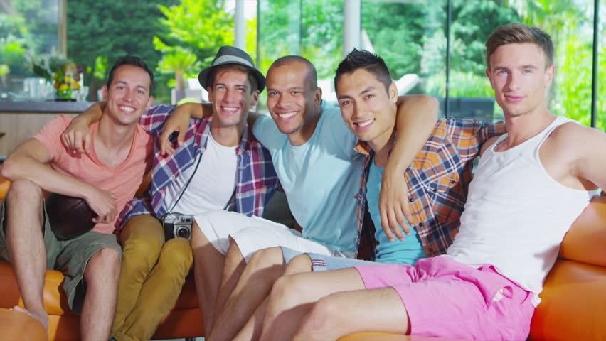 Portrait of happy group of young friends hanging out together in modern home