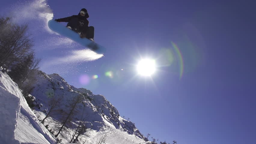 SLOW MOTION: Snowboarder jumping over the sun #5125496