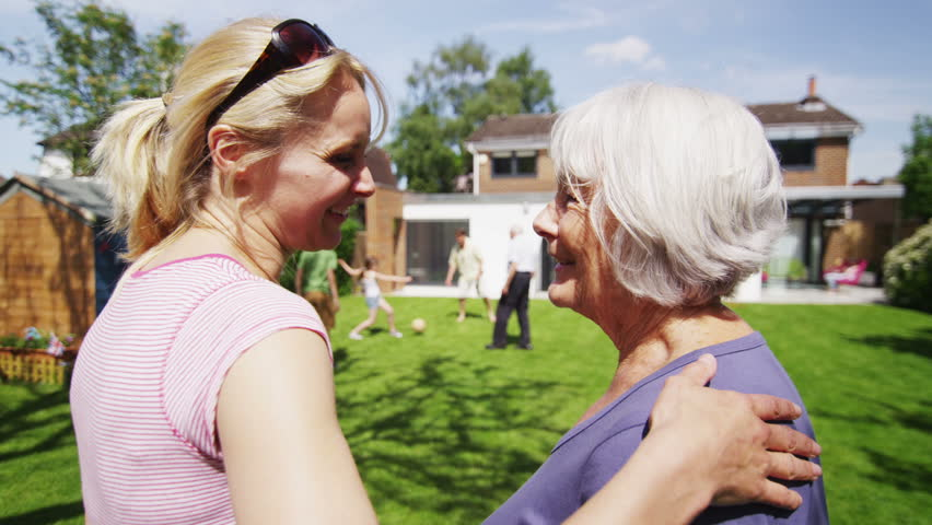 A daughter and her elderly mother bonding together as they watch the rest of the family playing in the garden at home. In slow motion. | Shutterstock Video #5131595