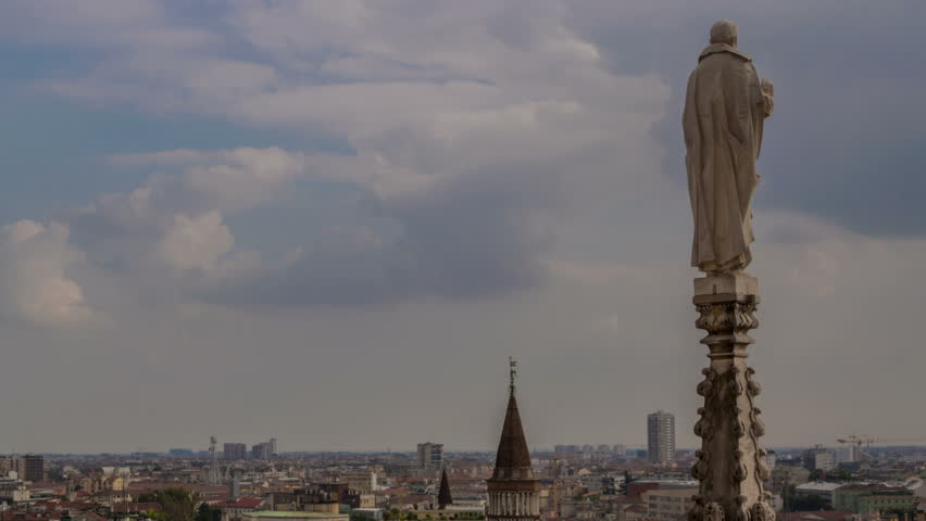 Italy Milan skyline from the top of Duomo cathedral  with back of statue of saint in foreground time lapse