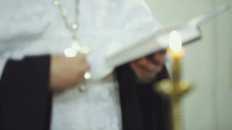 Priest prays with the Bible in the hands of. FullHD