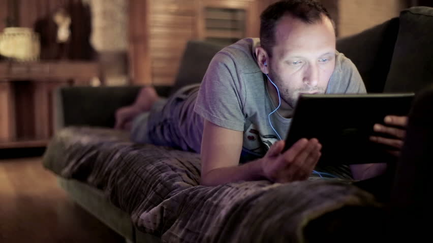 Young man watching movie on tablet computer on sofa