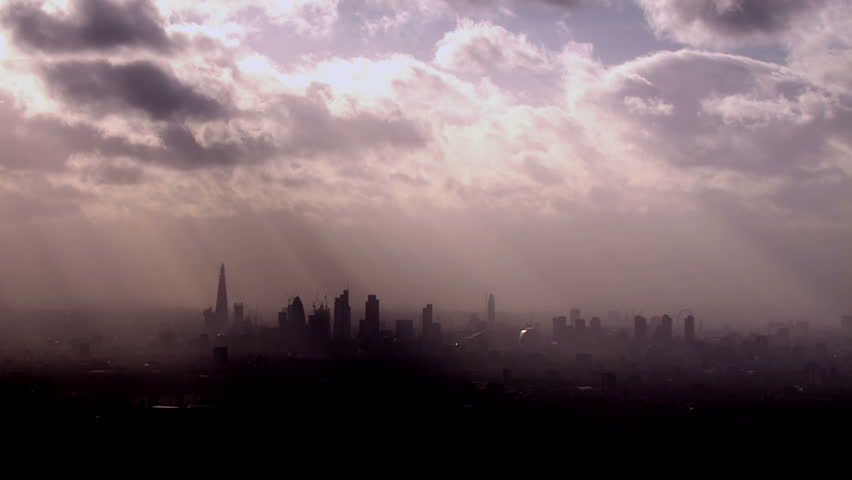Dramatic aerial view of the London skyline on a hazy autumn morning with rays of light beaming through the clouds above.