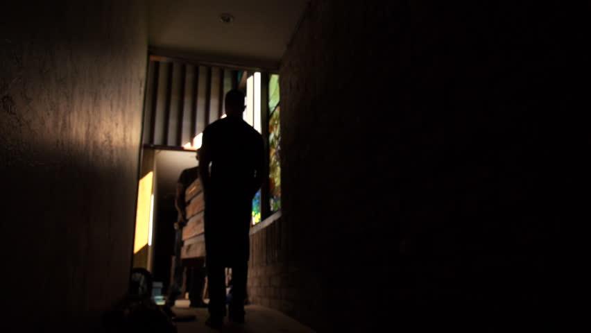 Men carry large wooden box down dimly lit corridor