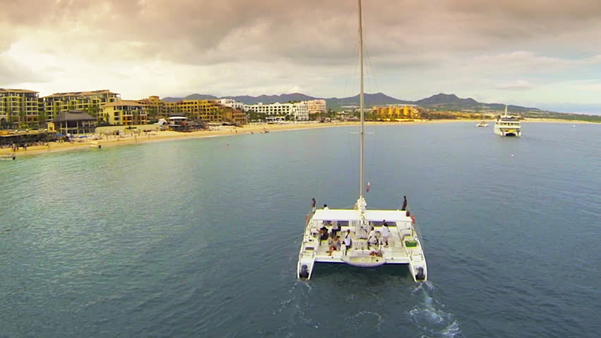Catamaran aerial chase on the ocean at sunset in Cabo San Lucas Mexico
