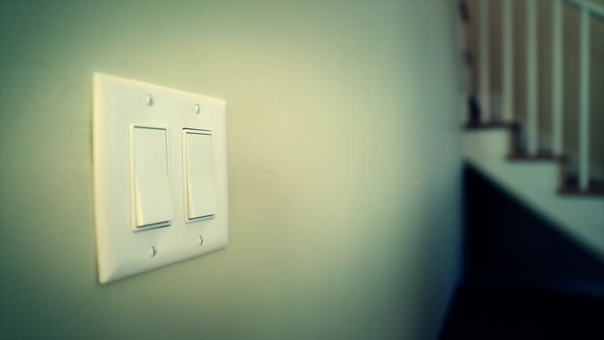 A hand turning on and off a light switch in a house