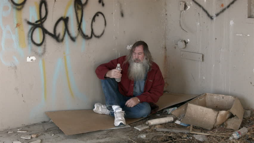 Abandoned building homeless man in corner water bottle HD. Homeless man long hair beard sad and poor sleeping. Man down on luck, poor, hungry and depressed sits on discarded cardboard in urban city.